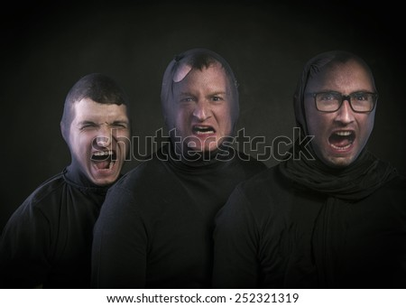 Three thieves in balaclavas on their faces, dressed in black. Studio shot on black background.