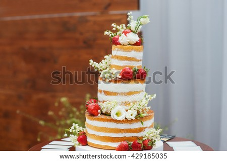 three-tiered wedding cake with strawberries on table - stock photo