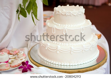 Three tiered wedding cake with white icing - stock photo