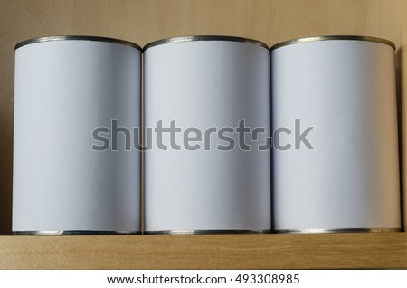 Three tin cans in a row, on a shelf above eye level, with blank white labels for copy space.