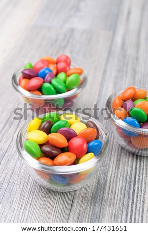 Three tiny bowls with multicolor candies - stock photo