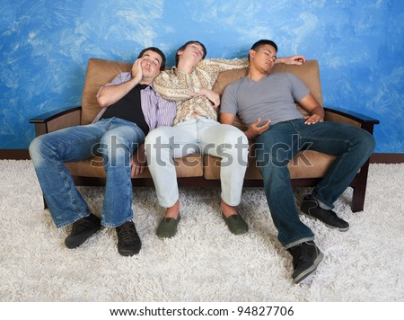Three tired young men sleep on a sofa - stock photo