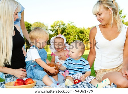 Three toddlers and their moms having lunch in the backyard - stock photo