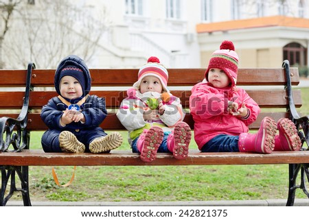 three toddlers are sitting on the bench - stock photo