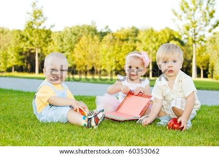 Three toddlers sitting on grass - stock photo
