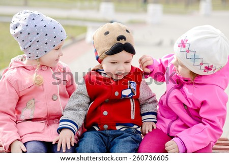 three toddlers sitting on the bench in the park - stock photo