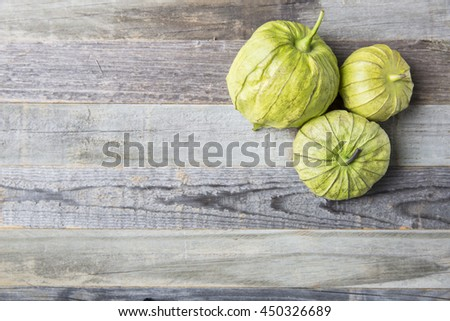 Three tomatillos on wooden surface with copy space.