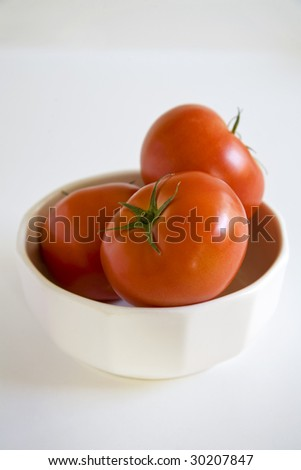 Three tomatoes on a kitchen countertop - stock photo