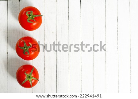 three tomatoes on wooden table - stock photo