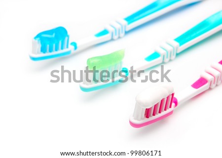 Three toothbrushes red, green and blue with toothpaste on a white background