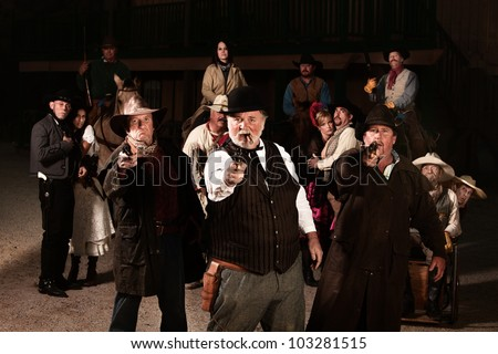 Three tough gunfighters in old American west town - stock photo