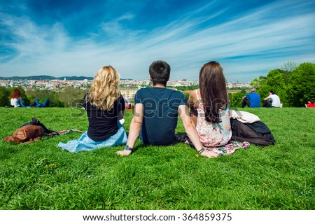 Three tourists friend sitting on the green grass with beautiful view to Vienna panorama - stock photo
