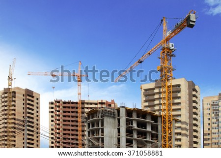 Three tower cranes on the background of buildings under construction.