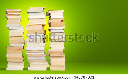 three towers of books on green background - stock photo
