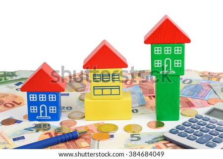 Three toy houses sitting on Euro notes and coins, with a calculator to symbolize home finance. - stock photo