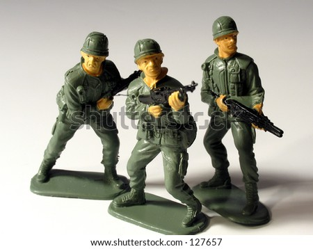 Three toy soldiers on white background - stock photo