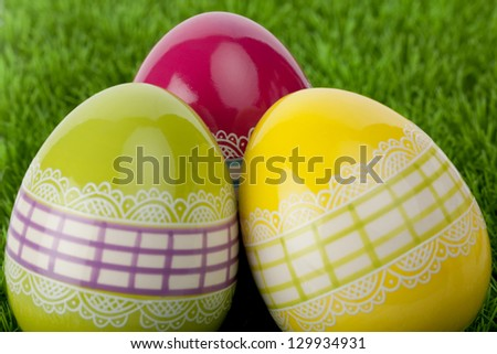 Three traditional decorative Easter eggs on grass, close up - stock photo