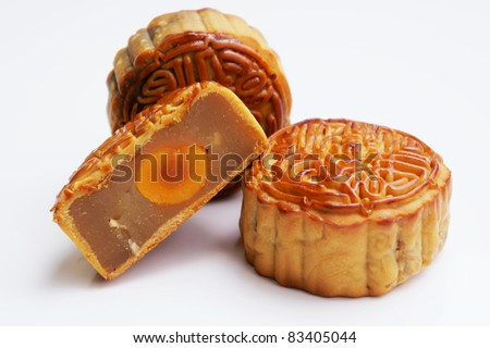 Three Traditional Mooncakes with one cut up half to show egg yolk - stock photo