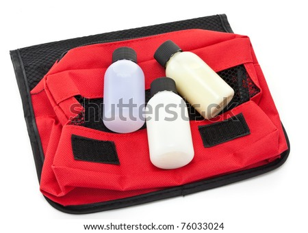 Three travel sized toiletry items on a red toiletries bag - stock photo