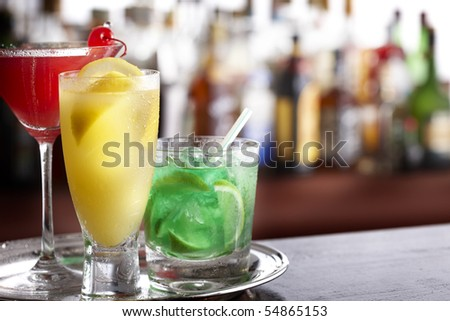 Three tropical mixed drinks sitting on silver tray, shot in bar with space for copy - stock photo