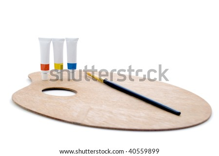 Three tubes of paint (primary colors) and a black/gold paintbrush, standing on a wooden artist's palette, isolated against a white background.  Shadows visible.  Whole composition in frame. - stock photo