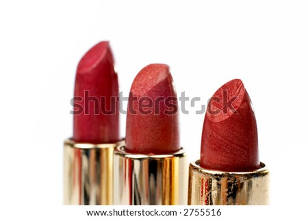 Three tubes of red lipstick. Macro shot (small DOF), with focus at front