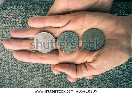 Three Tunisian coins on the woman's palm.