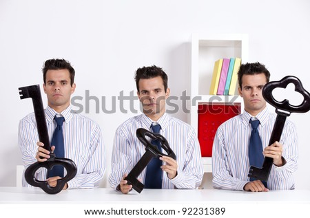 Three twin businessman at the office holding a giant key - stock photo