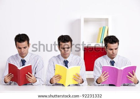 Three twin businessman at the office reading books - stock photo