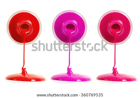 Three types of nail polish pouring from a bottle - stock photo