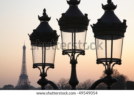 Three unlit street lamps at dusk, with the Eiffel Tower in the background. Horizontal shot. - stock photo