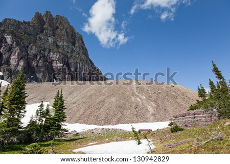 Three unrecognizable people hike along a ridge of eroded rock at the base of a giant rock mountain that makes them look super small in Glacier National Park, Montana. - stock photo