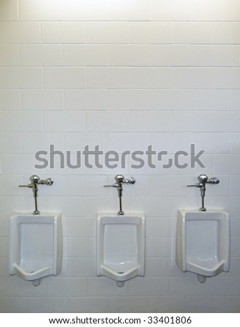 Three urinals with a white brick background - stock photo