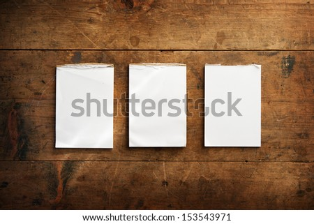 Three used memo pads on an old grungy wooden surface. For inserting your messages.  - stock photo
