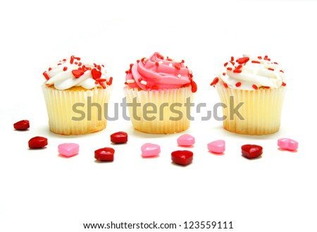 Three Valentines Day cupcakes with candies over white