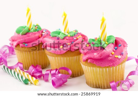 Three vanilla birthday cupcakes with pink and green frosting,  sprinkles, and birthday candles, copy space