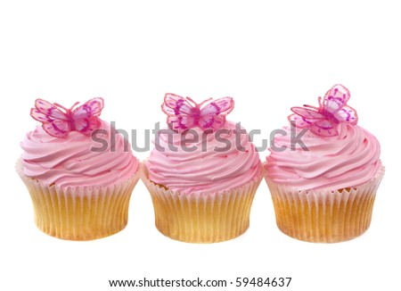 Three vanilla cupcakes decorated with pink frosting and little butterflies.  Isolated on white.