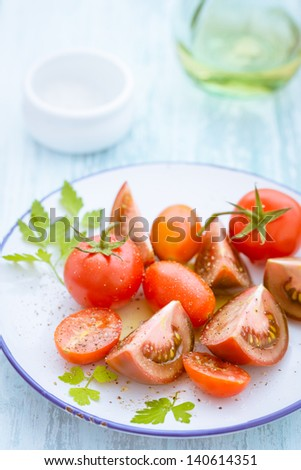 Three varieties of sliced and quartered tomato on a plate including grape tomatoes and cherry tomatoes - stock photo