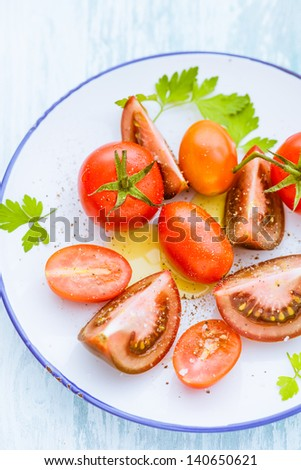 Three varieties of whole and halved tomato on a plate including grape tomatoes, cherry tomatoes and a purple-red variety - stock photo
