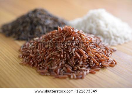Three variety of rice: red rice, wild rice, and white rice. Shallow DOF - stock photo