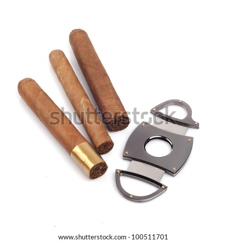 Three various cigars and a cutter isolated on white background - stock photo