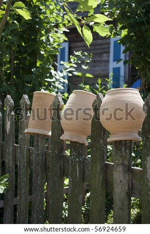Three various traditional clay pots hung on a fence in the countryside