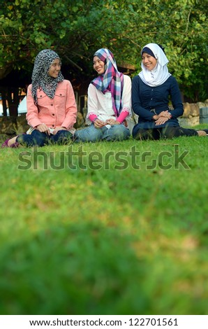 Three veiled girls were relaxing and chatting in the park