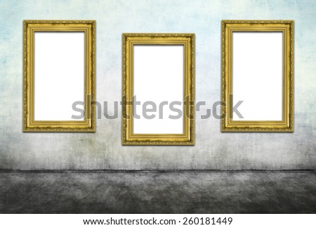 Three vertical golden frames on dirty wall - stock photo