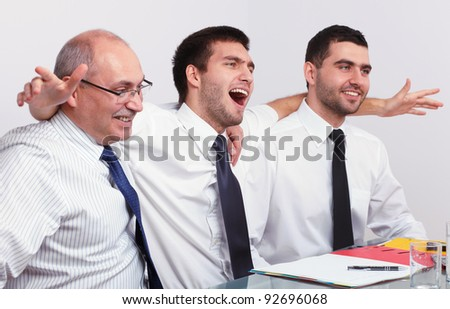 Three very happy and enthusiastic businessman during business meeting - stock photo