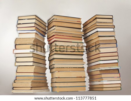 Three very high stack of books on a gray background