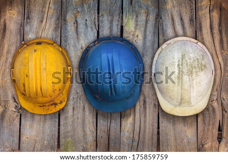 Three vintage construction helmets hanging on an old wooden wall - stock photo