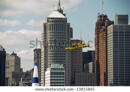 Three vintage Royal Canadian Air Force planes flying past the city of detroit during the Red Bull Air Race.