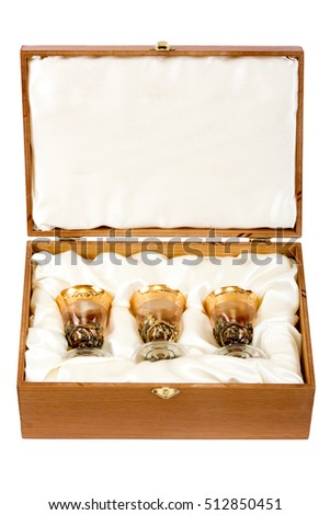 Three vintage shot glasses with gold plating in wooden box on white background