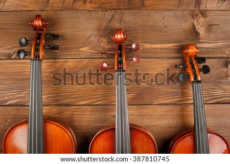 three violins in wood background - stock photo